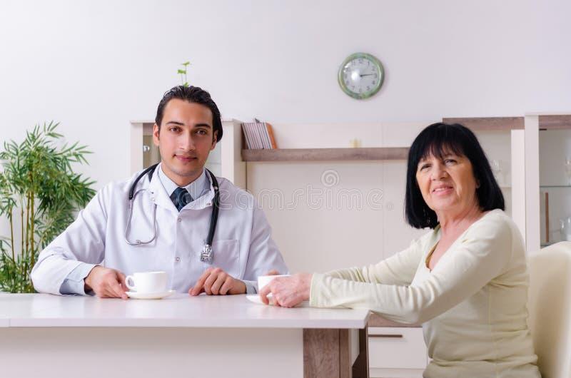Ung doktor som undersöker den höga gamla kvinnan royaltyfri bild