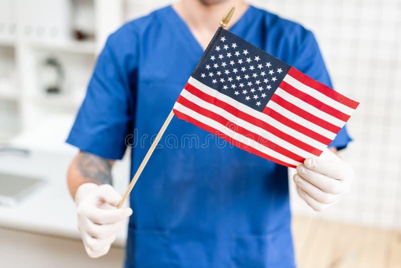 Ung doktorsman som rymmer en amerikanska flaggan i sjukhuset royaltyfri bild
