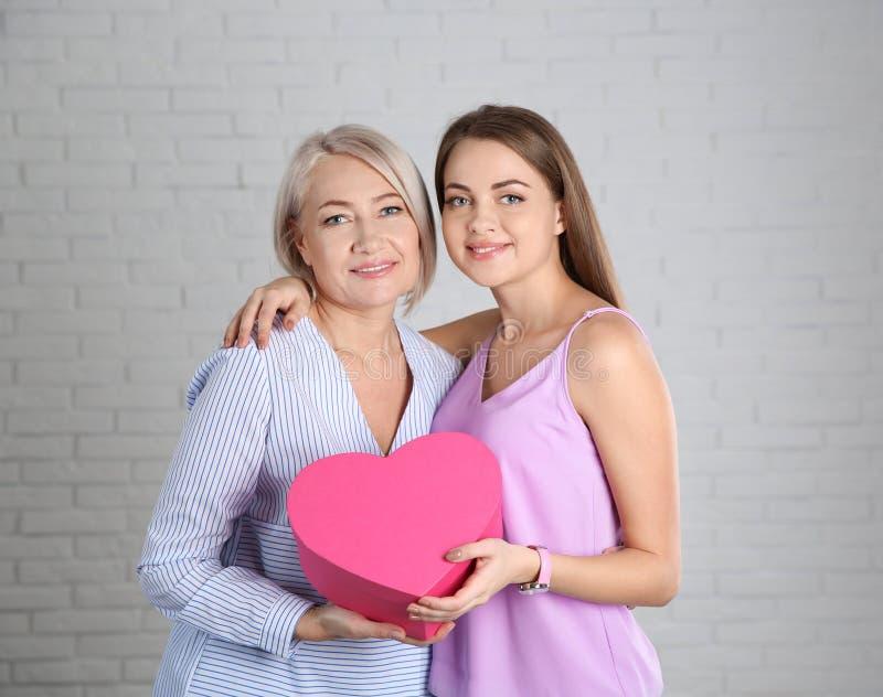 Ung dotter som gratulerar hennes mogna moder nära väggen Lycklig dag för kvinna` s fotografering för bildbyråer