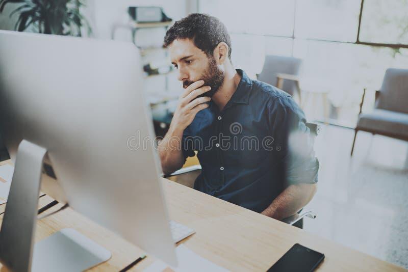Ung eftertänksam affärsman som arbetar på det soliga kontoret, medan sitta på trätabellen Mannen analyserar dokumentet på skrivbo royaltyfri bild