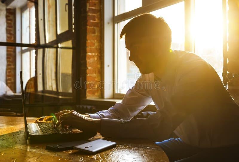 Ung eftertänksam coworker som arbetar på den soliga vinden för arbetsställe, medan sitta på trätabellen Mannen analyserar dokumen arkivbild