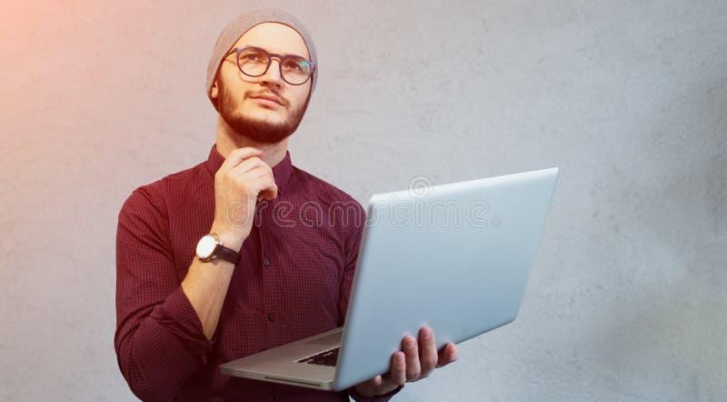 Ung eftertänksam grabbinnehavbärbar dator i händer över vit bakgrund Hatt för iklädd skjorta och silver, bärande exponeringsglas royaltyfri bild