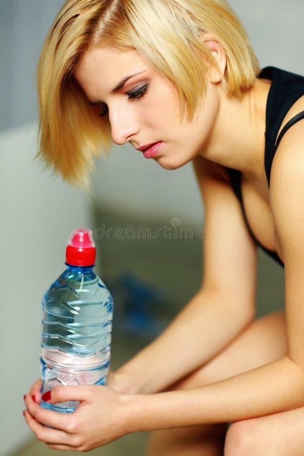 Ung eftertänksam kvinna med flaskan av vatten arkivfoto
