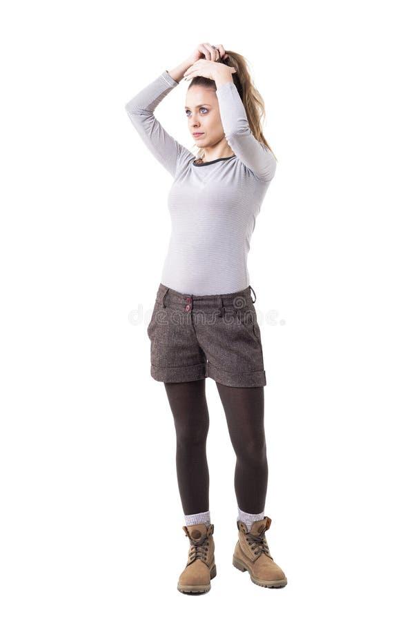 Ung eftertänksam lång hårhipsterflicka som gör frisyren som hänsynsfullt ser upp fotografering för bildbyråer