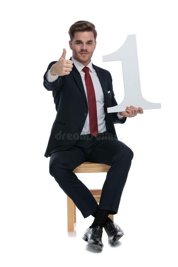 Ung elegant affärsman med nummer ett tecken royaltyfri fotografi