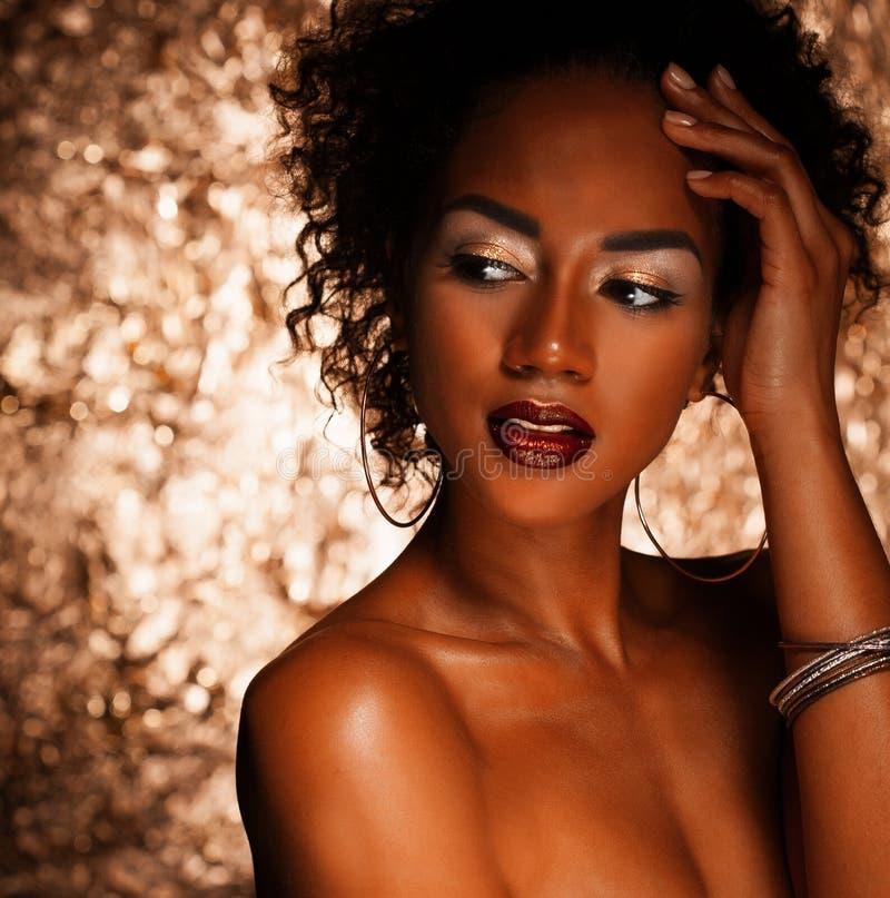 Ung elegant afrikansk amerikankvinna med afro hår Spika manicured polermedel spikar guld- bakgrund arkivfoton