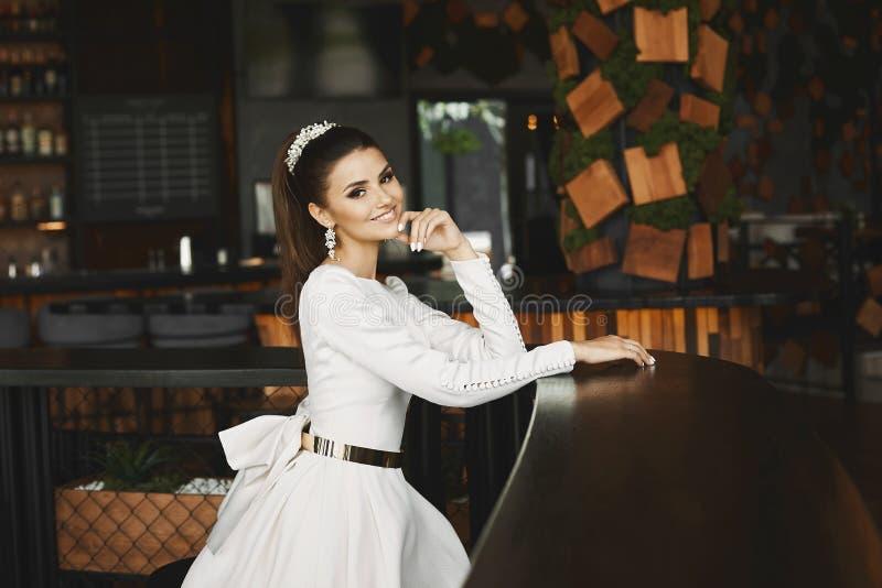 Ung elegant härlig och sexig brunettmodellkvinna i den vita klänningen med guld- bältesammanträde i stång och att vänta på arkivfoton