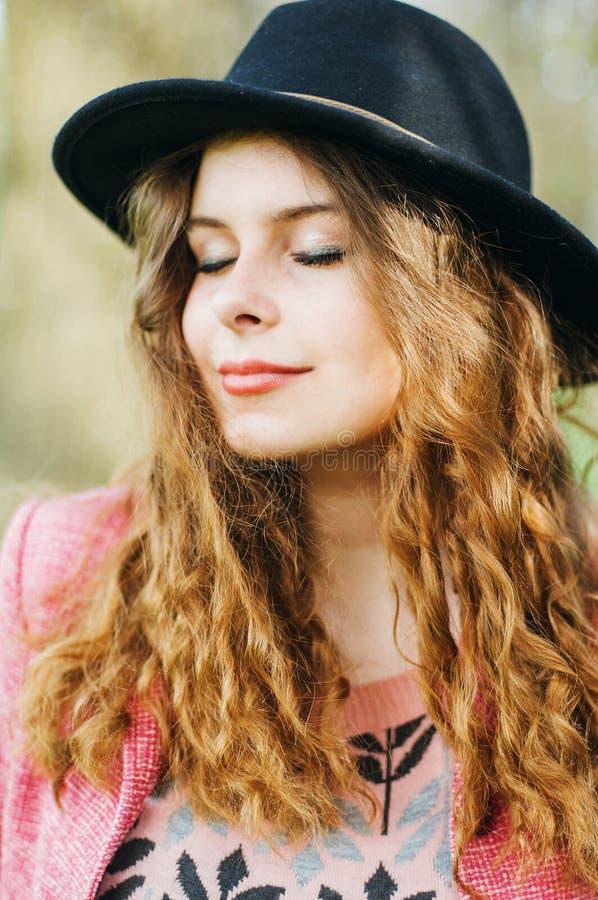 Ung elegant kvinna för stående i rosa färglag och svart hatt Mode royaltyfria bilder
