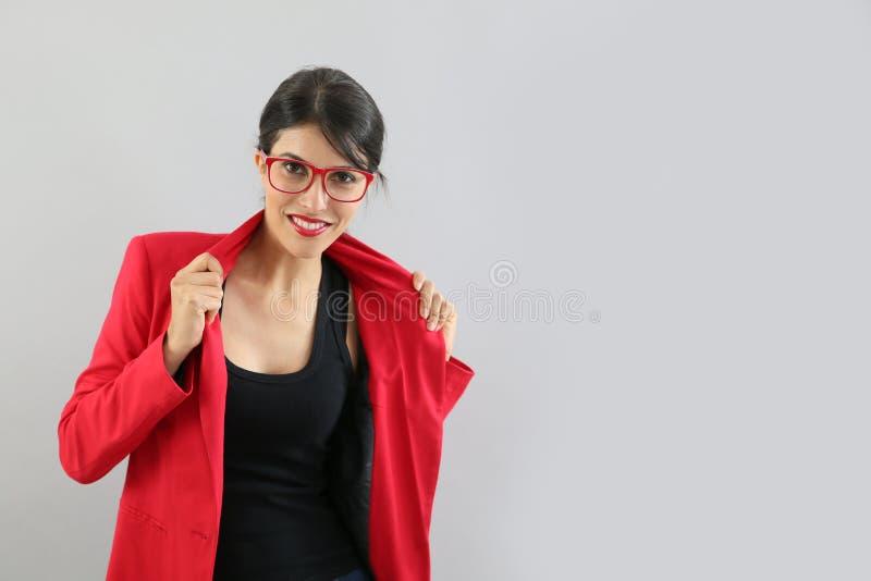 Ung elegant kvinna med det röda omslaget på grå bakgrund royaltyfria foton