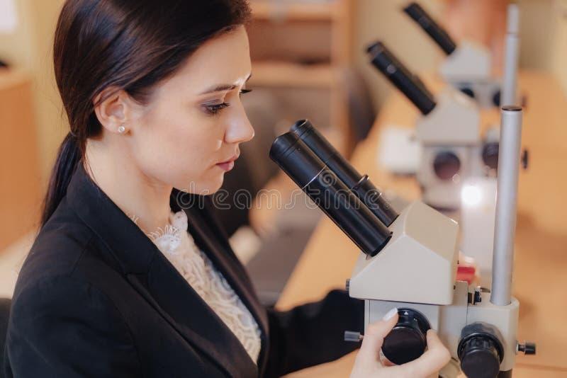 Ung emotionell attraktiv flicka som sitter på tabellen och arbetar med ett mikroskop i ett moderna kontor eller åhörare royaltyfri bild