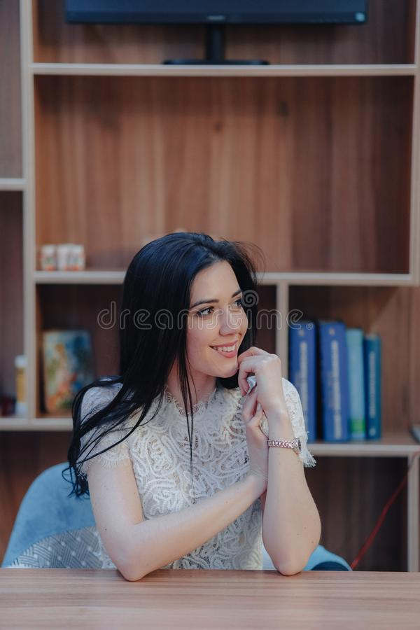Ung emotionell attraktiv flicka som sitter p? ett skrivbord i ett modern kontor eller salong royaltyfri fotografi