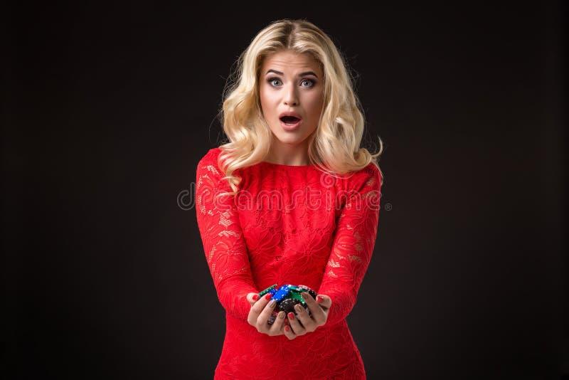 Ung emotionell kvinna som rymmer en grupp av chiper i hennes händer poker royaltyfri fotografi