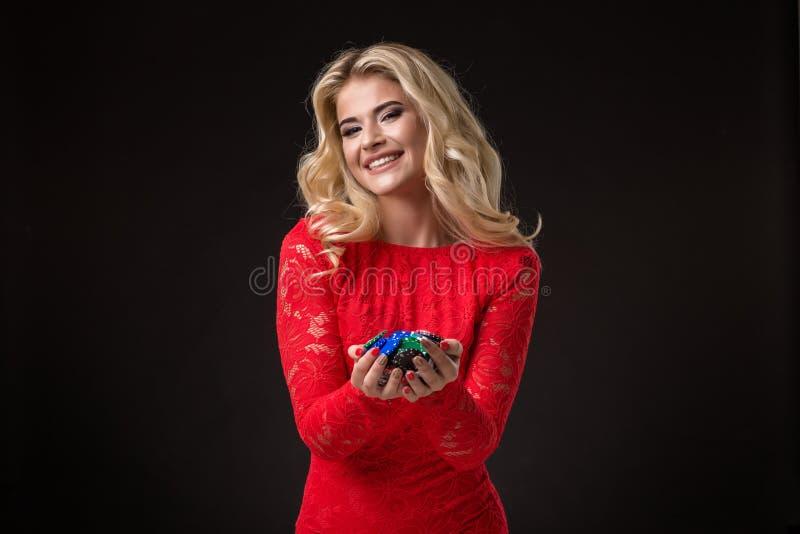 Ung emotionell kvinna som rymmer en grupp av chiper i hennes händer poker royaltyfri bild