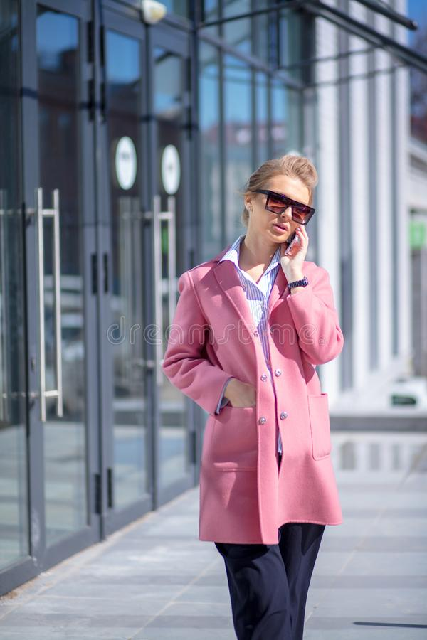 Ung enorm kvinna som använder hennes smarta telefon i gata royaltyfria foton