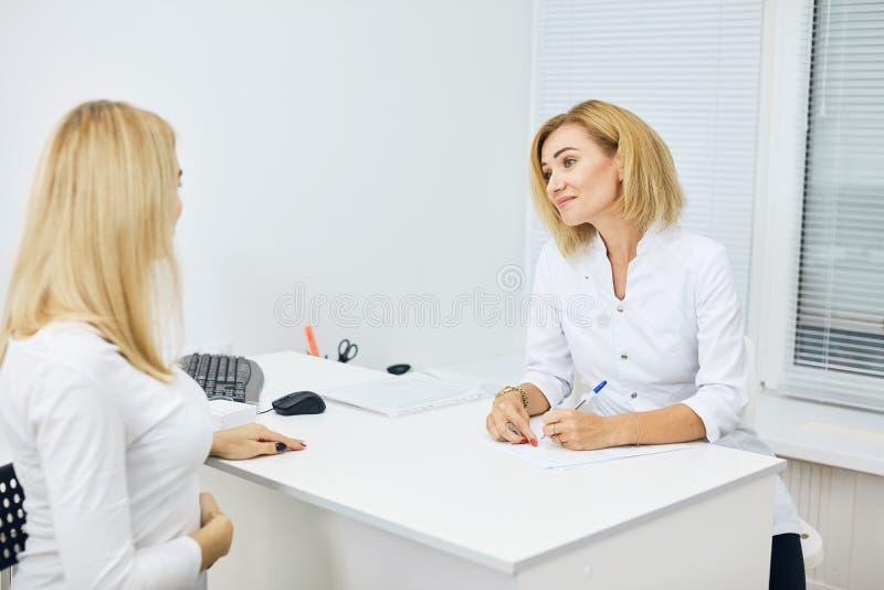 Ung enorm terapeut som ger rekommendationer till en gravid kvinna arkivbilder