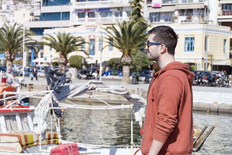 Ung ensam man på en port i Kavala, Grekland royaltyfria bilder