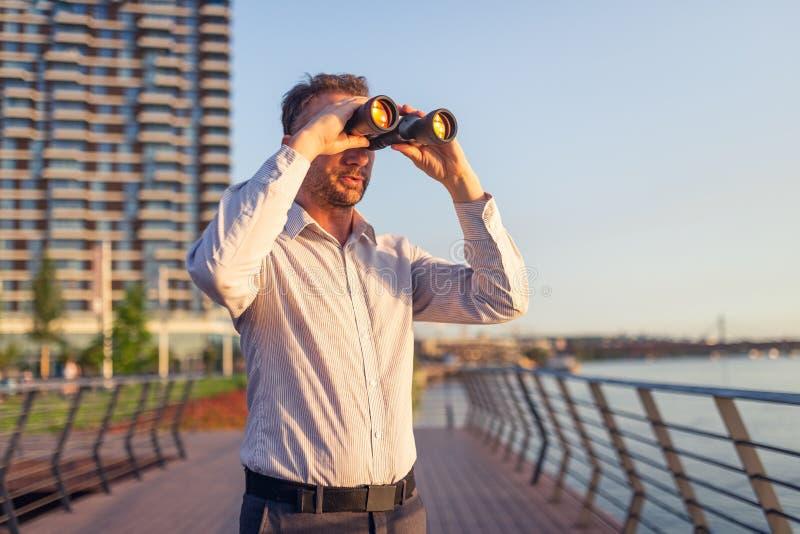 Ung entreprenör med kikare som spionerar på idérikt begrepp för konkurrenter arkivbild