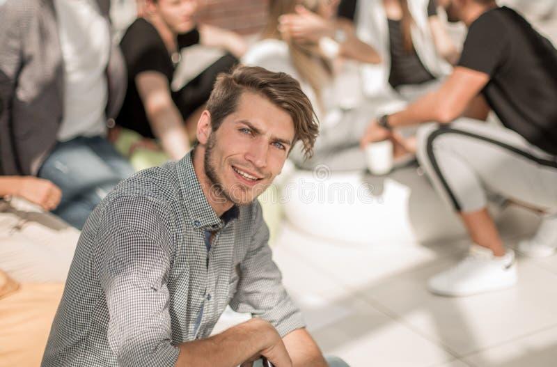 Ung entreprenör på bakgrunden av en grupp av unga formgivare royaltyfri bild
