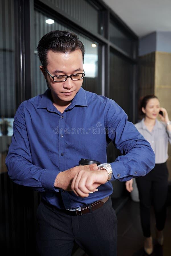 Ung entreprenör som kontrollerar tid arkivbild