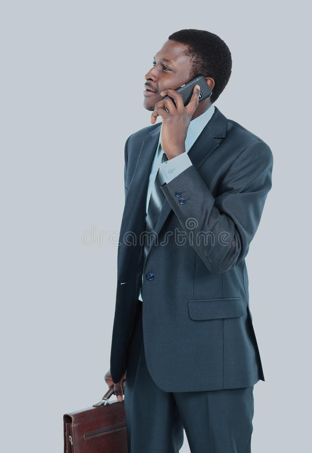 Ung entreprenör som rymmer hans lag över skuldra, medan tala på mobiltelefonen royaltyfria foton