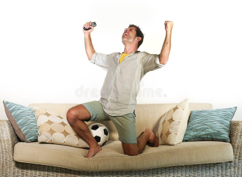 Ung entusiastisk fotbollsfan som firar galen lycklig banhoppning för mål på leken för fotboll för soffasoffa den hemmastadda håll arkivbilder