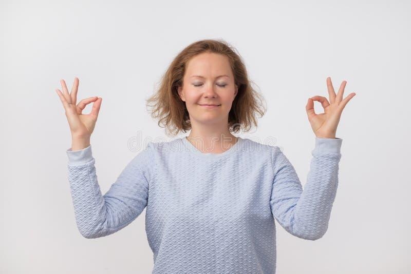 Ung europeisk le kvinna i rosa meditera för tröja som rymmer hennes händer i yogagest, kännande stillhet och realiteten arkivbilder
