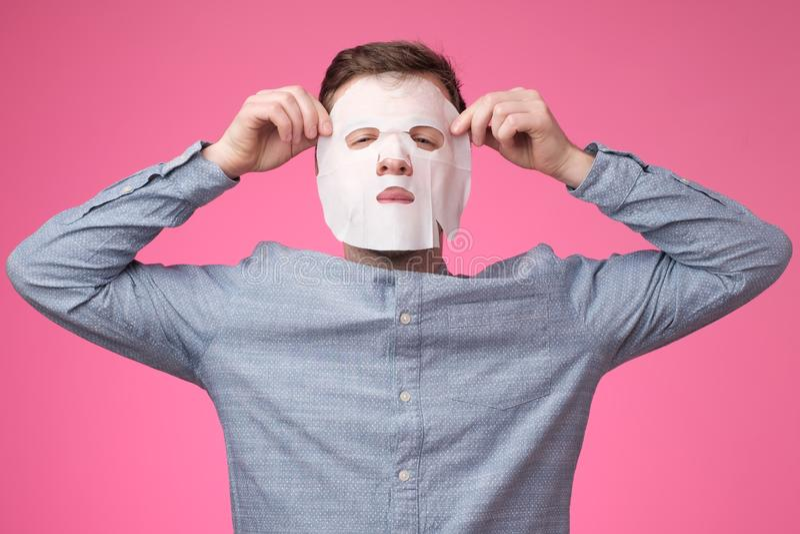 Ung europeisk man i ansikts- maskering på rosa bakgrund royaltyfri foto