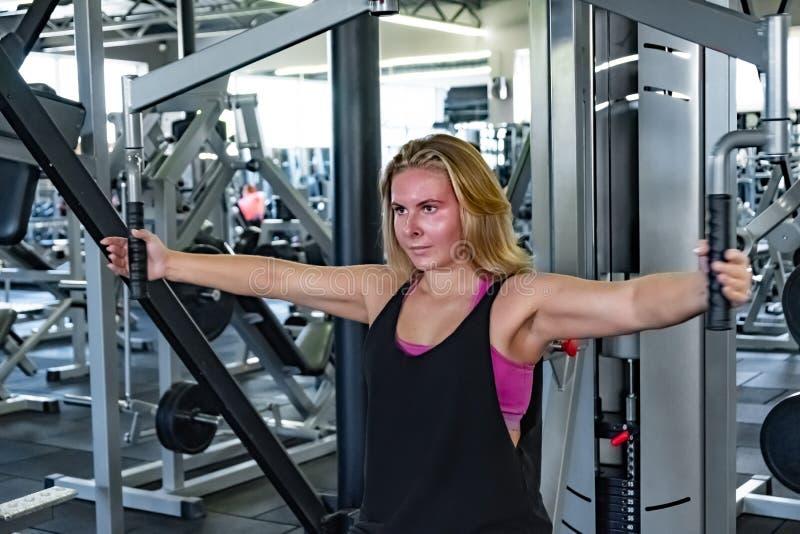 Ung färdig kvinna på idrottshallen som gör övning med horisontalbröstkorgen royaltyfria bilder