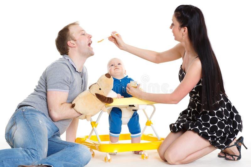 Ung föräldermatning behandla som ett barn. arkivbilder