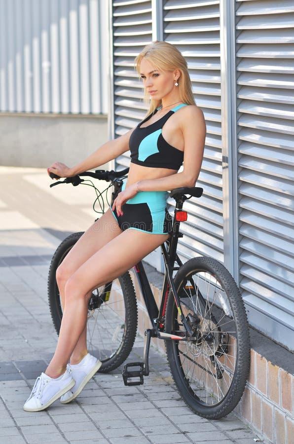 Ung förförisk blond kvinna i svart posera för sportkläder som är utomhus- royaltyfri fotografi