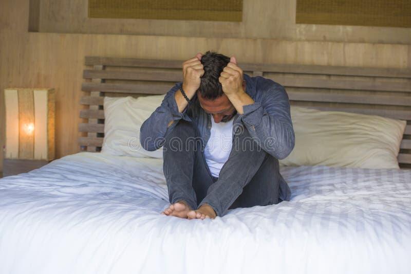 Ung förkrossad och deprimerad man som sitter på bekymrad säng och den frustrerade lidandefördjupningskrisen som drar hans hårkäns royaltyfria bilder