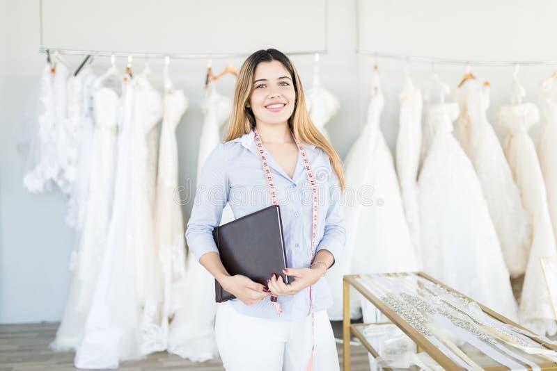 Ung försäljareSmiling In Wedding boutique royaltyfria foton