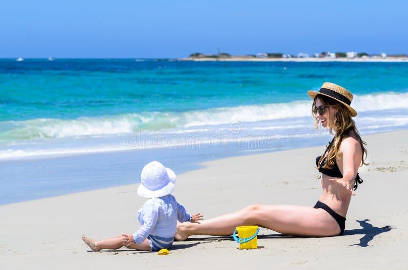 Ung förtjusande moder som har gyckel med den lilla dottern på den tropiska stranden royaltyfri fotografi