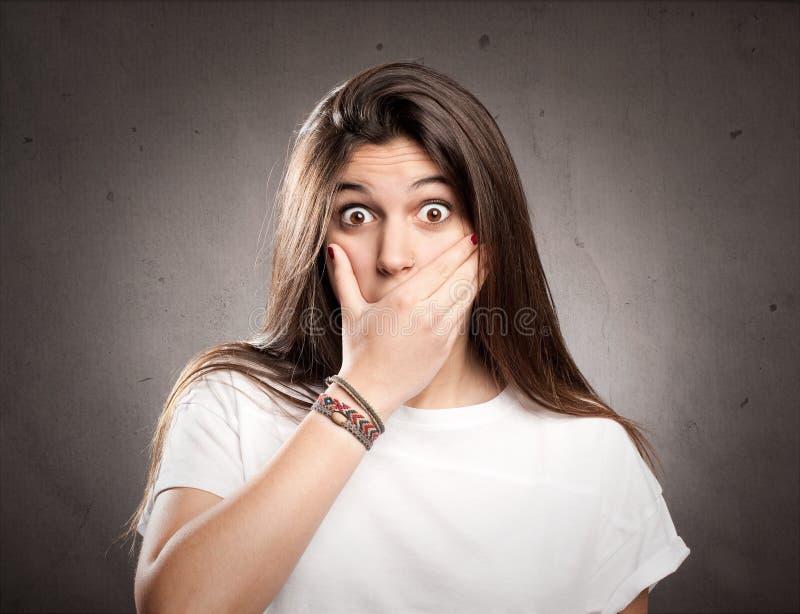 Ung förvånad flickabeläggningmun med hennes hand arkivfoton