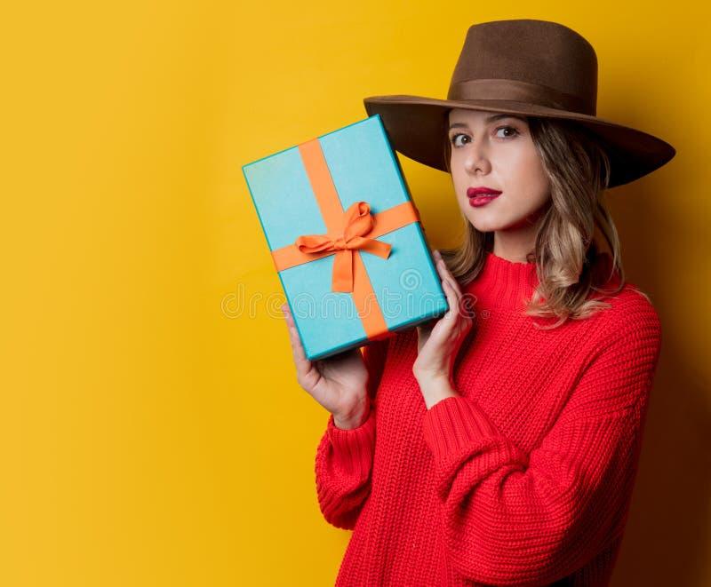 Ung förvånad kvinna i röd tröja med gåvaasken arkivfoton