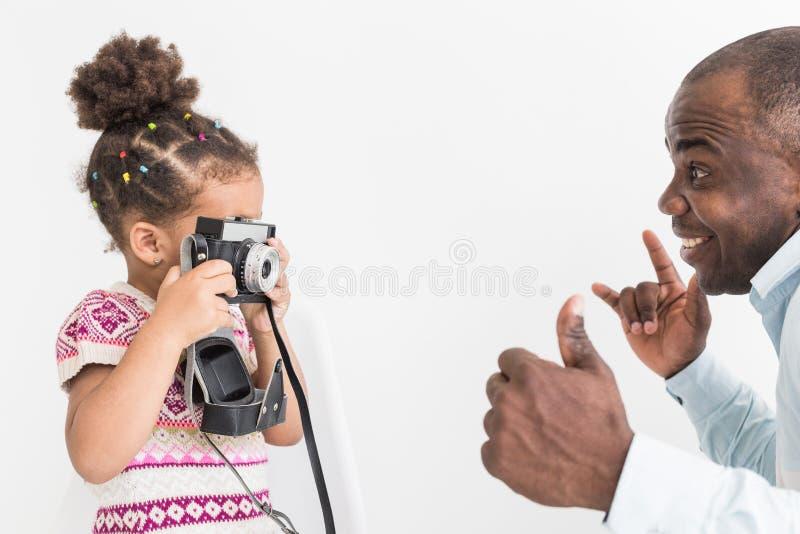 Ung fader med hans gulliga lilla dotter som tar bilder av de på en gammal tappningkamera royaltyfri bild