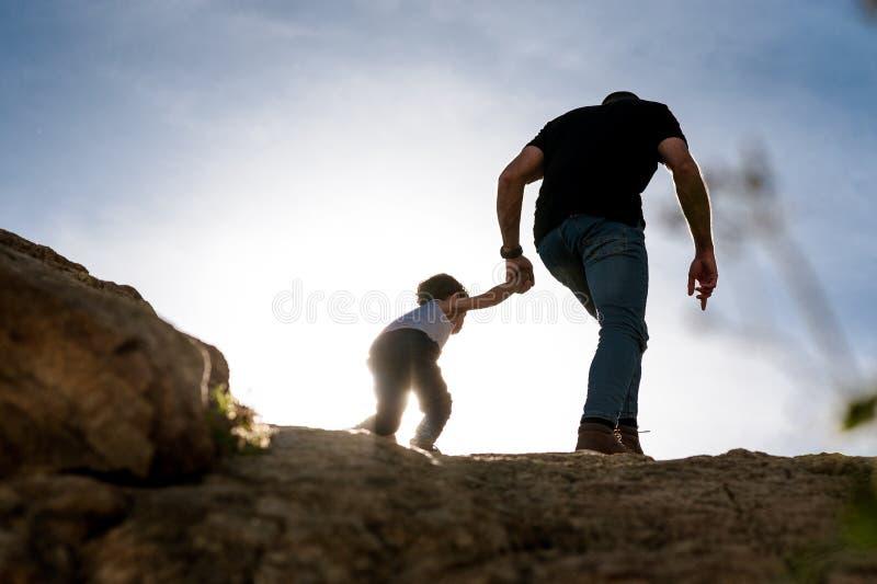 Ung fader som ger den hjälpande handen till hans son som går över bergöverkant som en metafor av faderskap arkivbild