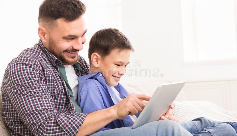 Ung fader som undervisar hans son att använda special applikation på den digitala minnestavlan royaltyfri bild