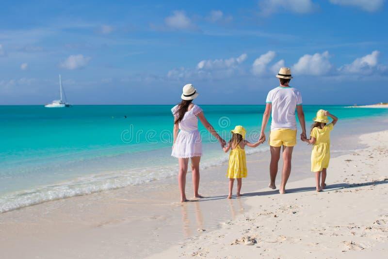 Ung familj för tillbaka sikt av fyra på den tropiska stranden royaltyfri fotografi