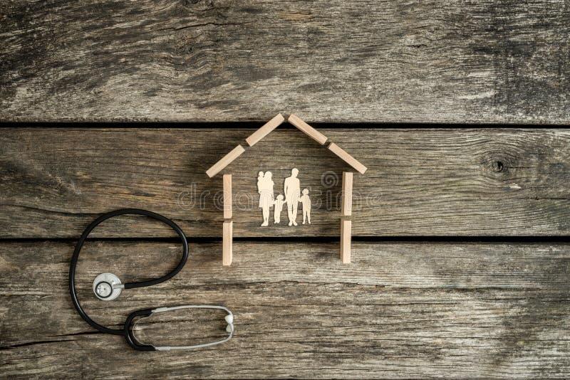 Ung familj i ett hus med stetoskopet royaltyfri foto
