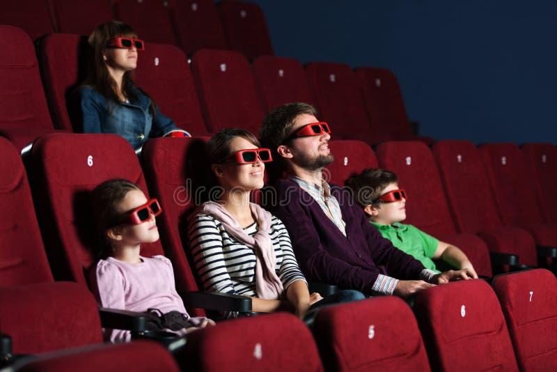 Ung familj i filmbiografen royaltyfri fotografi