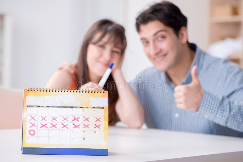 Ung familj i havandeskapplanläggningsbegrepp med ägglossningcalend arkivbilder