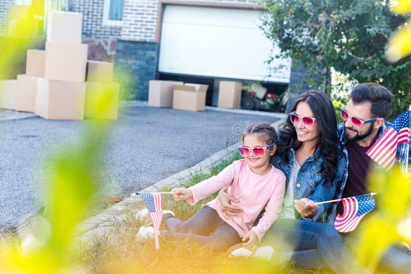 ung familj med amerikanska flaggan och solglasögon som sitter i trädgård av royaltyfri fotografi