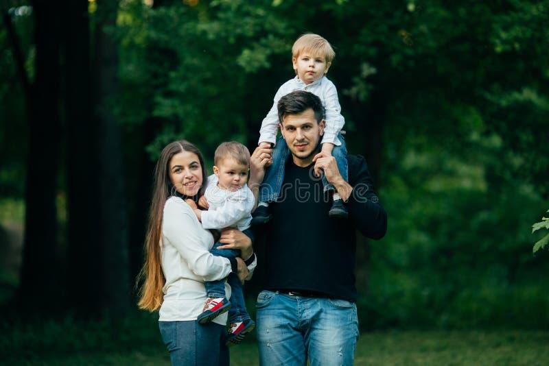 Ung familj med barn, den lyckliga fadern, modern och två söner som spenderar tid fotografering för bildbyråer