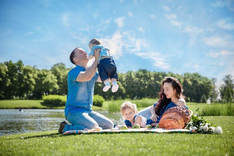 Ung familj med barn som har gyckel i natur royaltyfri foto