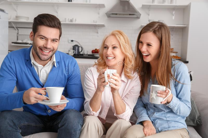 Ung familj med dricka för helg för svärmor hemmastatt arkivfoto