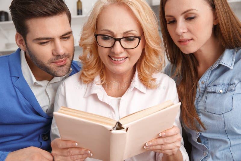 Ung familj med romanen för hemmastadd helg för svärmor den koncentrerade läs- royaltyfri bild