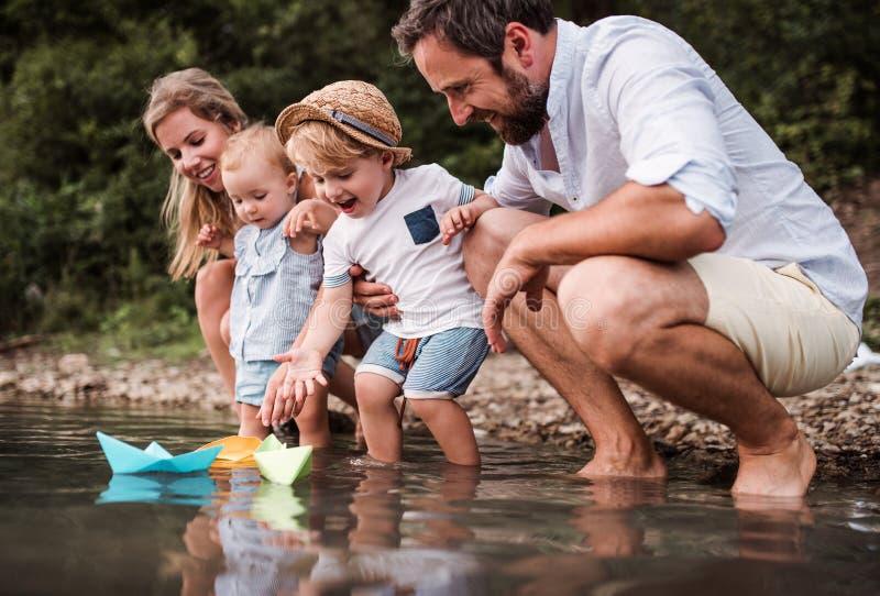 Ung familj med två litet barnbarn utomhus vid floden i sommar som spelar royaltyfria bilder