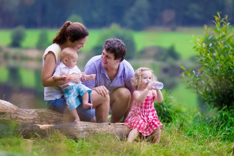 Ung familj med ungar som fotvandrar på en sjö royaltyfri bild
