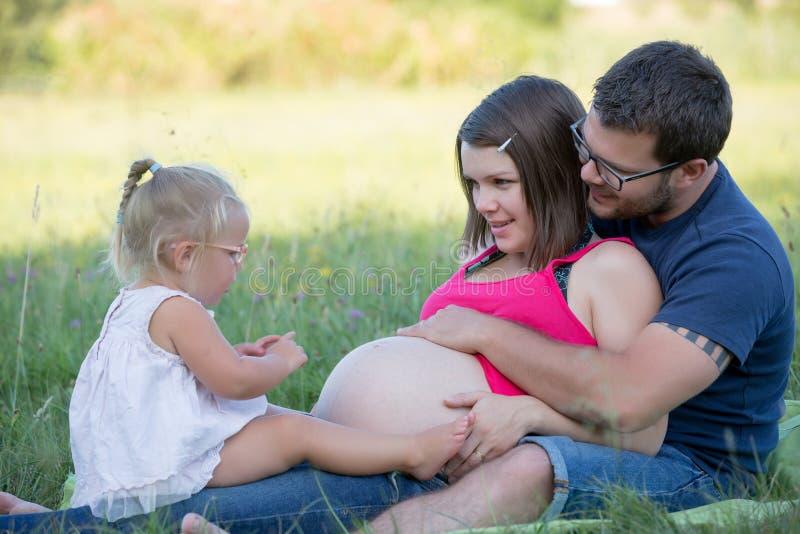 Ung familj med ungar som har picknicken utomhus royaltyfria bilder